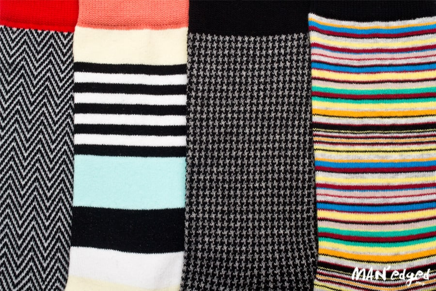 left close up of horizontal striped men's socks, thick striped men's socks in light color, houndstooth pattern men's sock, right multi-colored dress sock from related garments
