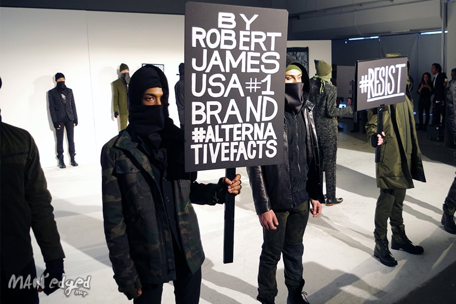 A shot showcasing various models holding political signage at men's fashion week.