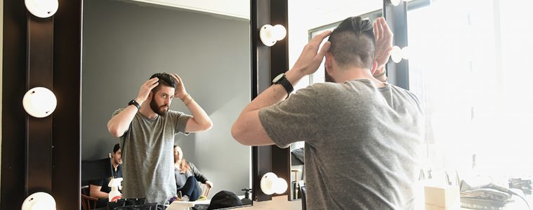 Guy in mirror styling hair, men's hair style