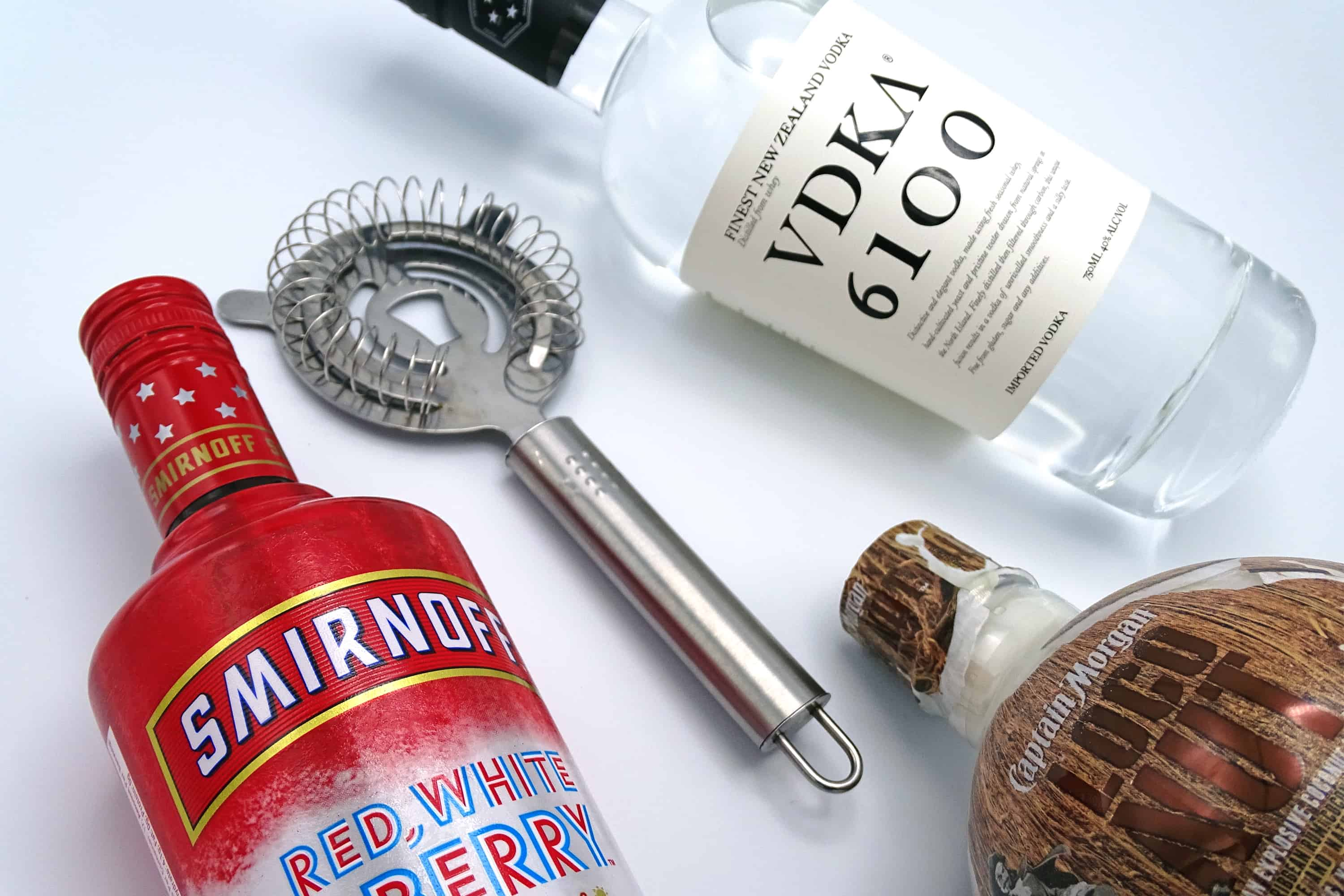 Best cocktails to celebrate 4th of July including: Smirnoff Red, White, and Berry bottle. Cocktail strainer. VDKA 6100 bottle. Captain Morgan Loco Nut bottle.