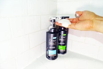 Man reaching for Dove Men+Care foaming body wash in shower